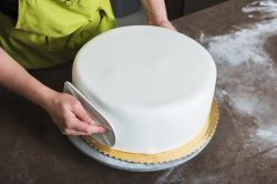 Smoothing Fondant on a Cake