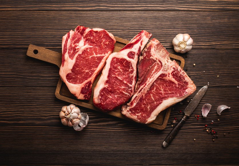Set of three different types raw meat steaks: Ribeye, T-bone, Cowboy on cut board with knife and seasonings, wooden background. Aged steaks assortment, butchery/restaurant concept, top view, close up.